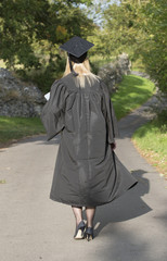 Mature University walking student wearing gown