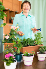 Smiling mature woman doing work in her small garden