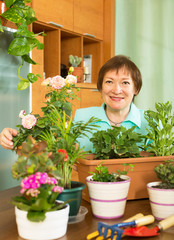 Smiling mature woman working with flowers