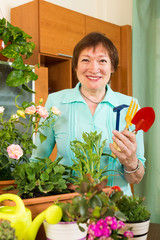 Female mature gardener with  plants in pots