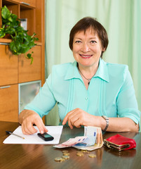 Portrait of positive female pensioner with cash and bills
