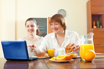 Two happy women using laptop during breakfast