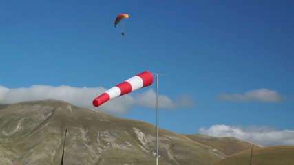 In mountains of Italy wind sleeve and paragliding