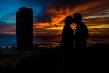 Liebespaar küsst sich bei Sonnenuntergang