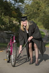 Cap and gown university student pumping tyre