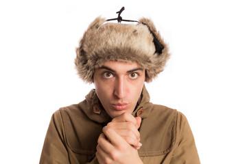 portrait of frozen man with eskimo hat, warm its hands