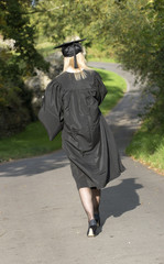Mature University student walking in gown