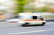 Ambulance in motion driving down the road - 70960547
