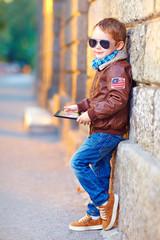 fashionable boy with digital tablet near the wall