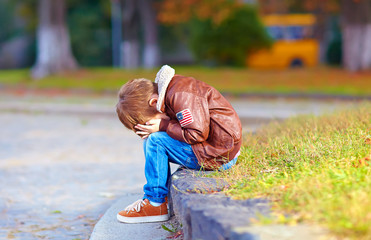 upset kid boy sitting alone in city park