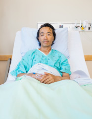 Male Patient Reclining On Bed In Hospital
