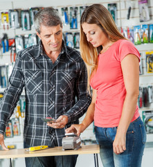 Couple Paying For Tools Through Smartphone In Store