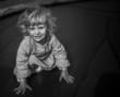 adorable blonde toddler girl sitting on a trampoline