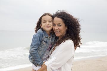 Madre sujetando en brazos a su hija en la playa