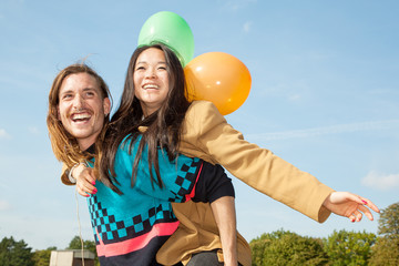 Man carrying young woman with balloons