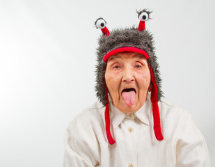 grandma in funny hat puts her tongue out