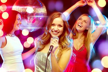 three smiling women dancing and singing karaoke