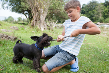 Young boy having fun with his dog outdoors