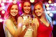 three smiling women with champagne glasses
