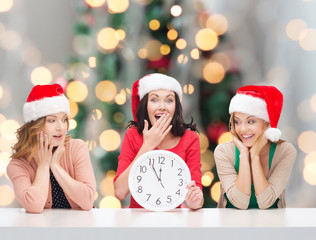 smiling women in santa helper hats with clock