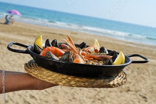 spanish paella on the beach - 70965316