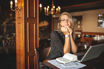 Business woman in glasses with laptop dreams in restaurant
