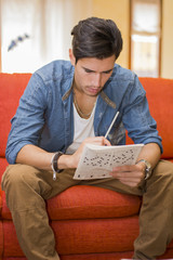 Young man sitting doing a crossword puzzle