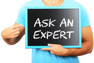 Man holding blackboard in hands and pointing the word ASK AN EXP