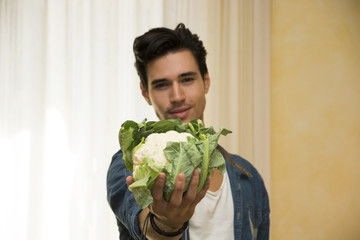 Smiling young man holding a fresh cauliflower in his hand
