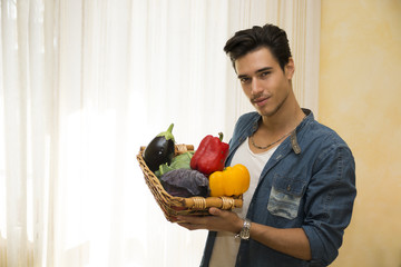 Young man holding basket of fresh vegetables, healthy diet