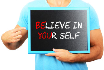 Man holding blackboard in hands and pointing the word BELIEVE IN