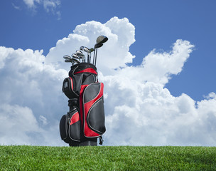 Golf clubs on grass with blue sky and clouds