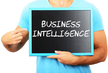 Man holding blackboard in hands and pointing the word BUSINESS I