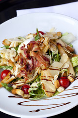 Salad with ham, parmesan, bacon, tomato, toasts and chicken