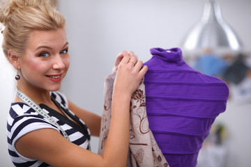 Smiling fashion designer fixing dress on  mannequin in a studio