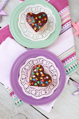Delicious rainbow cakes on plates, on color wooden background