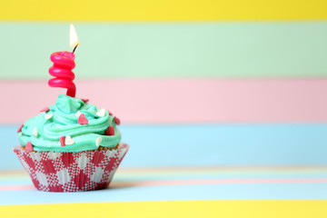 Delicious birthday cupcake on table on bright background