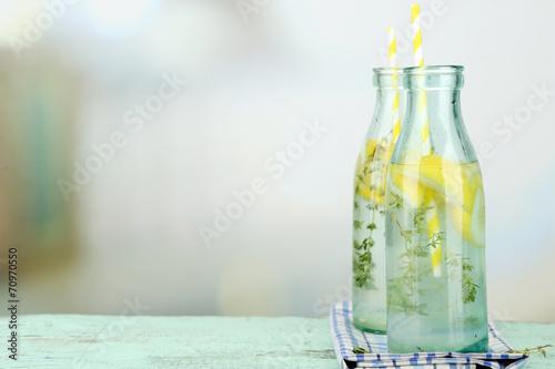 Leinwandbild Motiv Tasty cool beverage with lemon and thyme, on light background