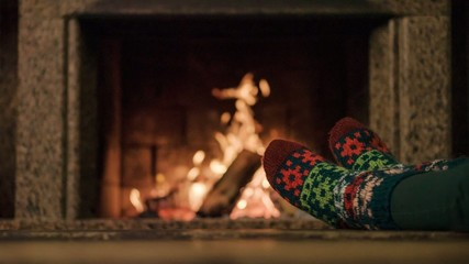 Woman relaxes by warm fire and wriggles her toes. Cozy evening