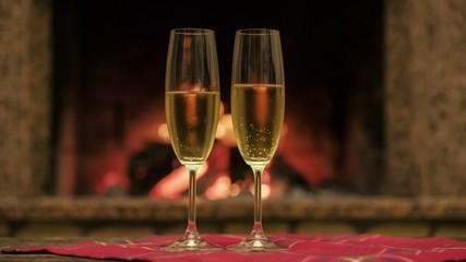 Couple taking glasses with champagne by the cozy warm fireplace.