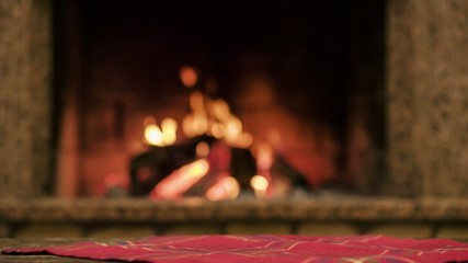 Couple toasting with champagne by the cozy fireplace. Close up.