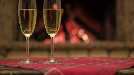 Champagne in glasses in front of the warm fireplace. Close up.