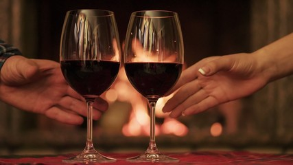 Couple taking glasses with red wine by the cozy fireplace.
