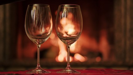 Pouring glasses of red wine by fireplace. Cozy romantic evening.