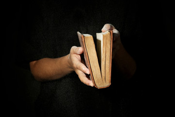 Woman holding very old book with dust, on dark background