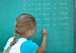 young girl student writing lines on chalkboard