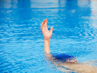 A hand of a drowning person stretching out of water.