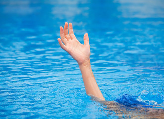 A hand of a drowning person stretching out of the water