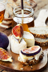 Breakfast setting with bread, cheese, figs and honey