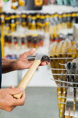Salesman Holding Hammer In Hardware Store